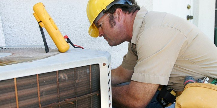 HVAC technician fixing AC unit