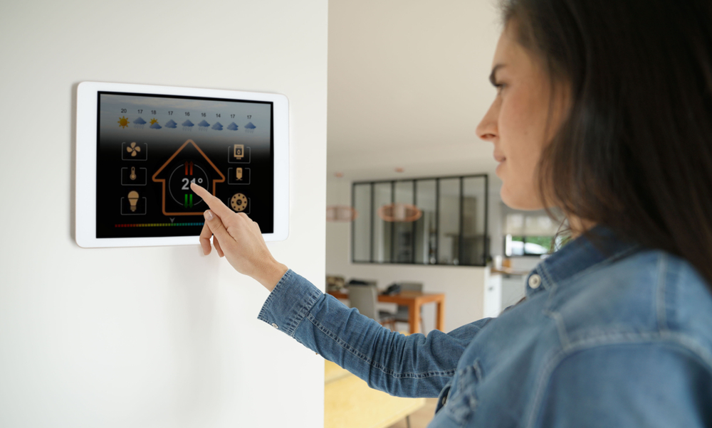 woman sets thermostat for high efficiency furnace