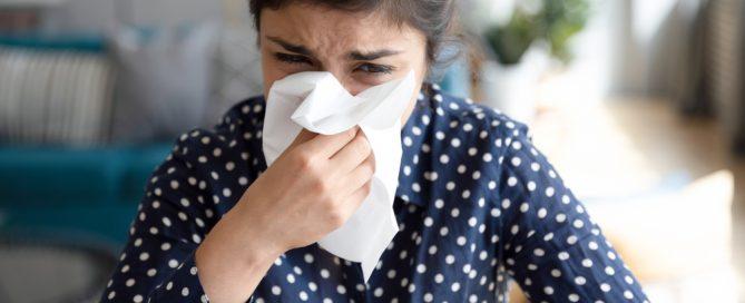 woman with allergies sneexzes