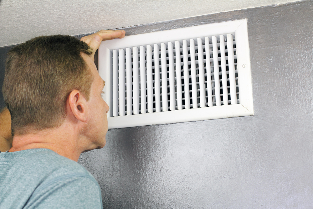 man suffering from allergies checks HVAC