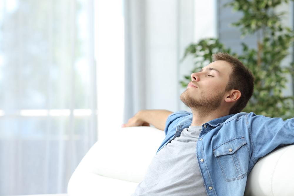 man breathing in clean air at home