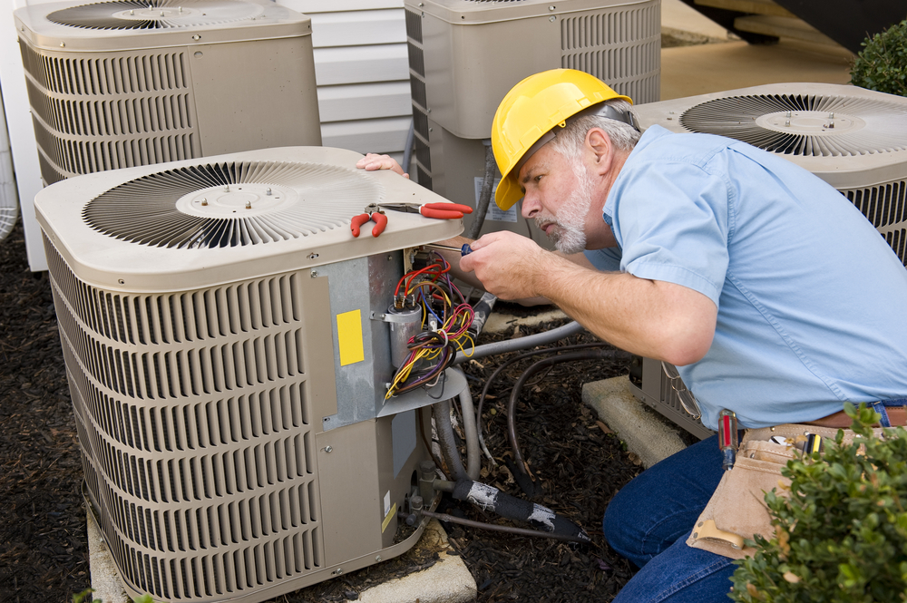 A/C tech works on air conditioner unit