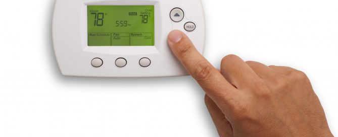 hand on thermostat adjust heat