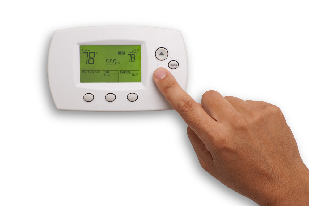 hand on thermostat adjust heat