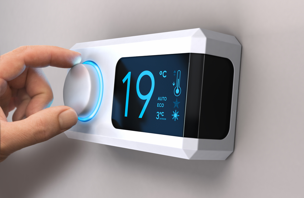 hand adjusts thermostat